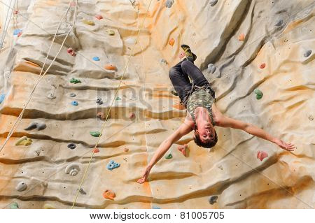 Man climbing on man-made cliff in the sport centre poster