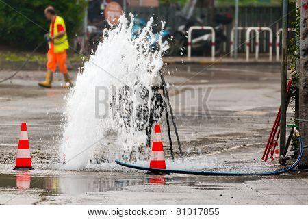 Road Spurt Water Beside Traffic Cones And A Technician In Background