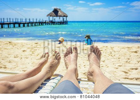 Tan Feet of a couple on lounge chairs enjoying a beach vacation while watching their kids play in the sand poster