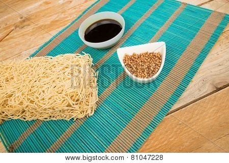 A buch of Chow Mein noodles and bowls with condiments poster