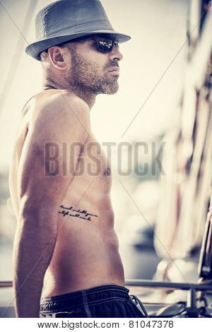 Vintage style photo of sexy shirtless sailor on sailboat, tanning man with stylish tattoo wearing trendy hat and sunglasses relaxation on luxury water transport