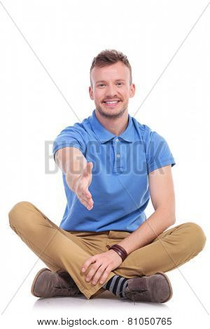 casual young man sitting on the floor with his legs crossed and offering you a friendly handshake, with a smile on his face. isolated on white