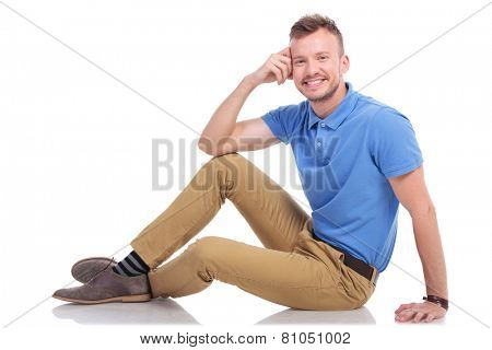 full length picture of a casual young man posing on the floor with a smile on his face and a hand at his head. on a white background