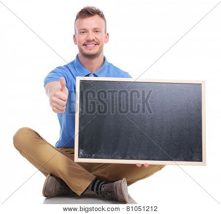picture of a casual young man sitting on the floor with his feet crossed while holding a small blackboard and showing the thumb up gesture. on a white background