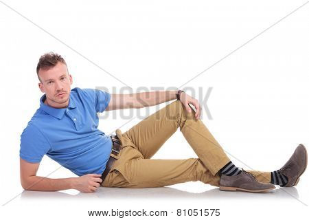 full length picture of a casual young man lying on the floor and looking into the camera with a serious expression on his face. on a white background