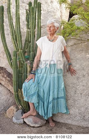 Portrait of a lovely and graceful senior woman in the desert garden wearing jewelry by Art Medicine Adornment. poster