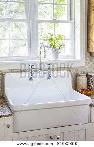 Kitchen interior with rustic white porcelain sink and granite stone countertop under large sunny window