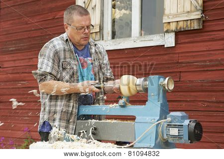 Man does carpenter work outside of his house in Korpilahti, Finland.