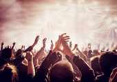 Vintage style photo of a crowd, happy people enjoying rock concert, raised up hands and clapping of pleasure, active night life concept poster