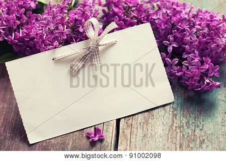 Postcard with fresh splendid lilac flowers and empty tag for your text on aged wooden background. Selective focus. Toned image. poster