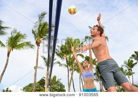 Friends playing beach volleyball sport in summer. Woman volley the ball to man jumping to smash. People having fun recreational volley ball game living healthy active sport lifestyle.