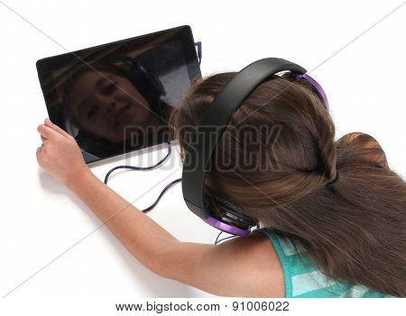 Beautiful pre-teen girl on the floor usin a tablet computer