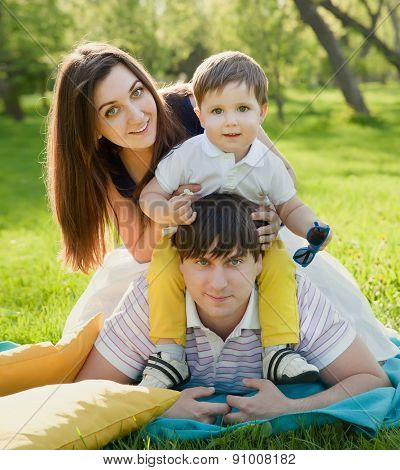 Happy family having fun outdoors in summer park against blurred leaves background