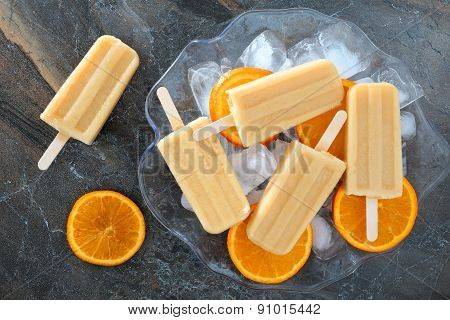 Homemade orange yogurt popsicles in an ice filled bowl
