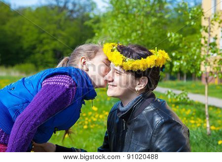 Daughter Kisses Mom In The Park