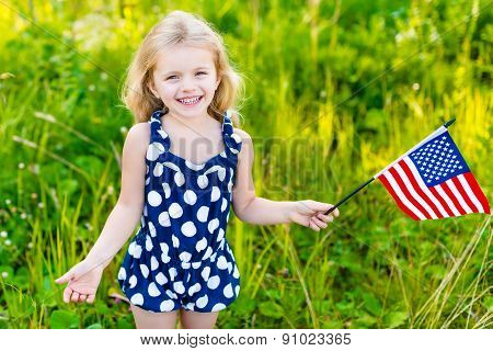 Smiling Little Girl With Long Curly Blond Hair Holding American Flag And Waving It, Outdoor Portrait