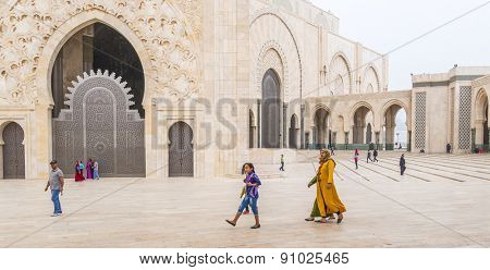 CASABLANCA, MOROCCO, APRIL 2, 2015: Local family walks on the outside grounds of Hassan II Mosque or Grande Mosquee Hassan II by misty morning
