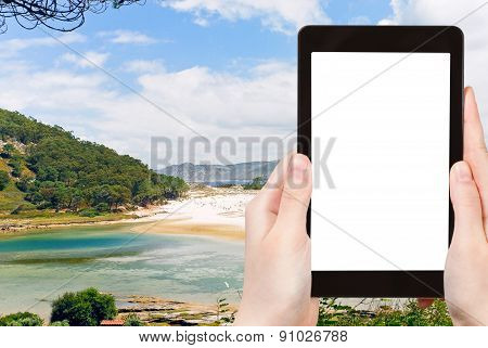 travel concept - tourist photograph Cies Islands (illas cies) - Galicia National Park in Atlantic Ocean Spain on tablet pc with cut out screen with blank place for advertising logo poster