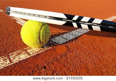 Close up view of tennis racket and ball on the clay tennis court