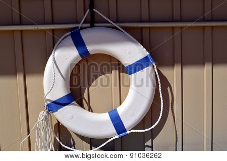lifebuoy with reflective tape hung up on a wall