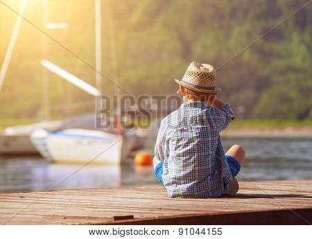 Boy On Wooden Pier Looking For A Yahts