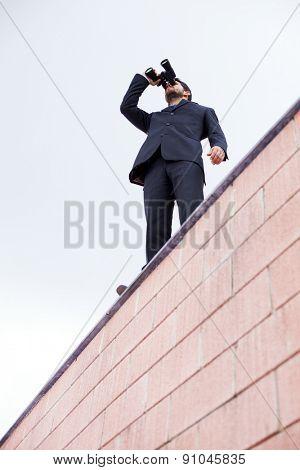 Businessman looking thought his binoculars