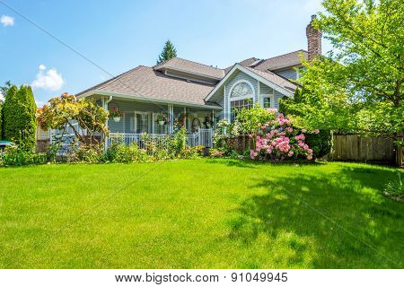 Entrance of a luxury house with a patio and beautiful landscaping on a bright sunny day. Home exterior. poster