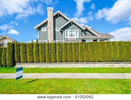 Beautiful house behind green hedge fence with empty for sale, lease, rent sign. Landscape trimming d