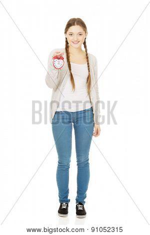 Beautiful teenage woman with alarmclock.
