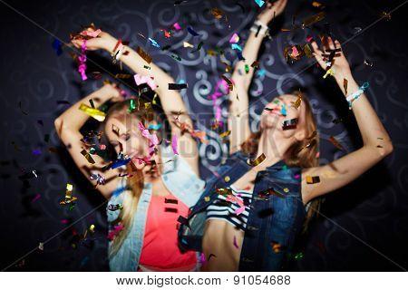 Two energetic girls dancing in confetti falling