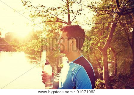Sport man drinking water bottle in a city park. Male runner athlete taking a break thirsty after run. poster