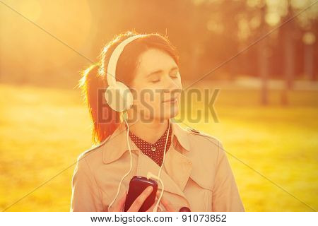 Woman listening to music in headphones in park  in sunlight in a sunny day. Young smiling businesswoman,student ,professional outdoors listening to music. Businesswoman smiling,Life style, poster
