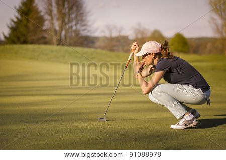Woman golf player crouching and study the green before putting shot.