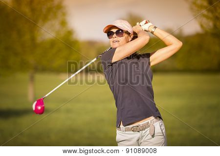 Female golf player swinging driver club from tee box at twilight.