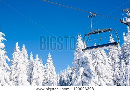 Ski resort image with chair lift and white snow pine trees