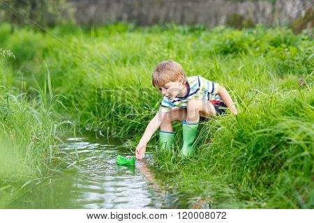 Cute little boy playing with paper boats by a river