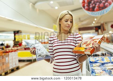 Beautiful woman deciding what to buy based on what is healthier