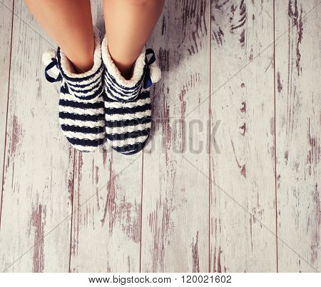 Warm slippers on the background old white floor. Homeliness.  poster
