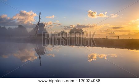 White Historic Windmill In Morning Fog