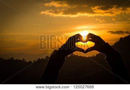 Silhouettes Hand Heart Shaped With Sun Sets And The Sky Orange