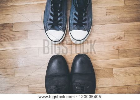 men black leather shoes and blue worn sneakers on parquet from above