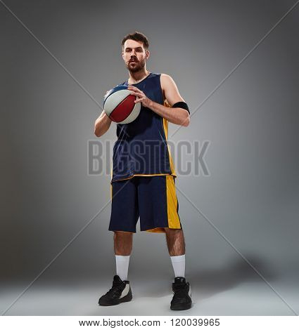 Full length portrait of a basketball player posing with ball