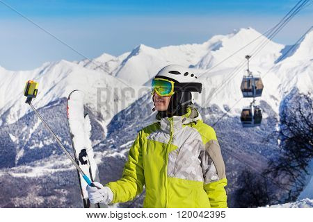 Skier young woman over mountains and cable car