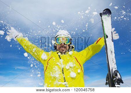Happy skier man throw snow over sky