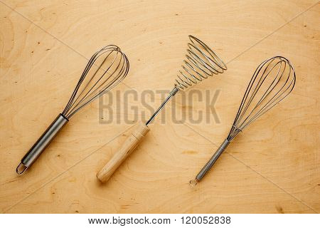 Metal whisk or eggbeater for whipping and whisking cooking ingredients lying on a textured wooden ba