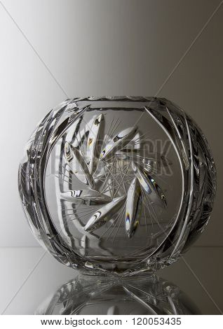 A big round vase stands on the glass table.