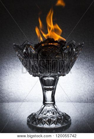 A big crystal vase with fire on the top stands on the glass table.