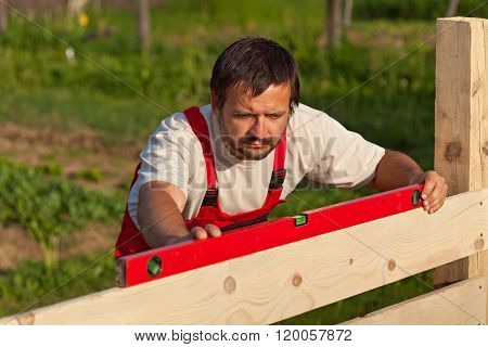 Worker Building Wooden Fence