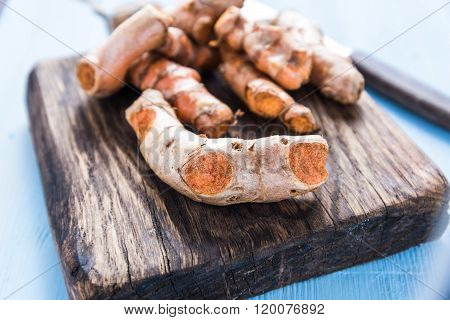 Garden Fresh Tumeric Spice Root On Wooden Board