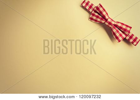 Red cell bow tie on beige background